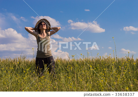 Young woman with hat enjoying the nature.  33638337