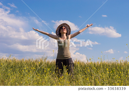 Young woman with hat enjoying the nature. 33638339