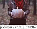 Woman holding big orange pumpkin 33638962