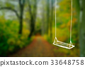 White wooden swing hanging on tree. 33648758