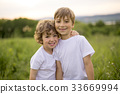 Brother play together in a green meadow 33669994