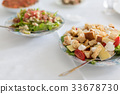 Salads in plates on a white table. 33678730