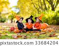 Kids with pumpkins in Halloween costumes 33684204
