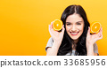 Happy young woman holding oranges  33685956