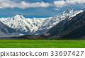 Mountain ranges and green grass field landscape 33697427