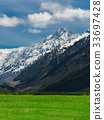 Mountain ranges and green grass field landscape 33697428