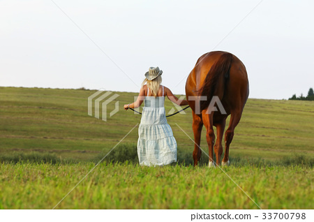 Woman in summer dress walk beside her horse 33700798
