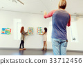 Young artists in gallery hanging painting on walls 33712456