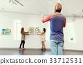 Young artists in gallery hanging painting on walls 33712531
