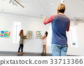 Young artists in gallery hanging painting on walls 33713366