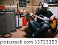 Bass guitarist playing guitar in music studio 33723353