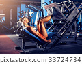 Woman doing fitness training on a leg extension 33724734
