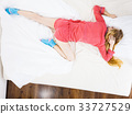 Young woman lying on bed wearing pajamas 33727529