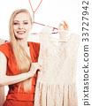 Woman in shop or wardrobe picking dress 33727942