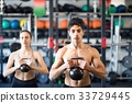 Young fit couple in gym exercising with kettlebell 33729445