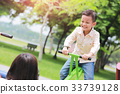 Mother with son playing seesaw in the park. 33739128