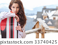 Standing beatiful young woman with a pink snowboard on snow. 33740425