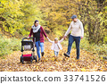 Beautiful young family on a walk in autumn forest. 33741526