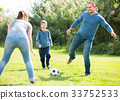 Glad son and parents playing football 33752533