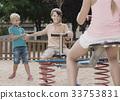 kids are teetering on the swing on the playground. 33753831