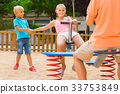 children are teetering on the swing in the playground. 33753849
