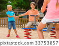children are teetering on the swing in the playground. 33753857