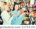 Happy female customers selecting chocolate 33754191