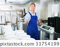 positive man seller standing with goods lift in housewares hypermarket 33754199