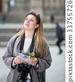 Blond adult girl holding brochure in hands 33755726
