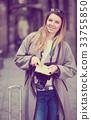 Blond happy girl holding brochure 33755850