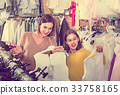 Mother and daughter choosing pretty dress 33758165