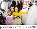 Family choosing dress in shop 33758200