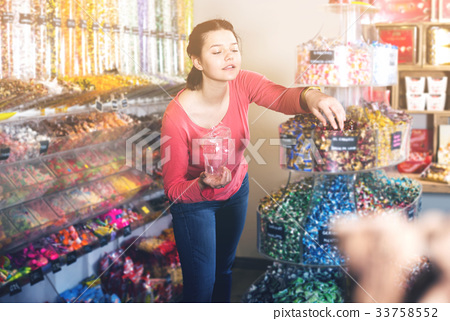 Woman posing to photographer picking different candies 33758552