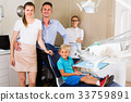 Young family is on dentist's receptionist 33759891