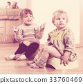 Two siblings sitting on chamber pots 33760469