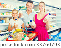 Happy young woman and man with child choosing yogurt 33760793