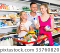 Young family with child choosing milk and other products 33760820
