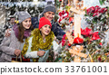 family of three with teenage girl choosing floral decorations at market. Shallow depth of focus 33761001
