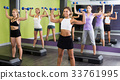 Young females performing aerobics with dumbbells 33761995