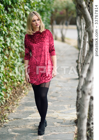 Beautiful young blonde woman in urban background 33767814