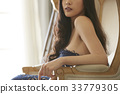 An elegant lady is posing and sitting on the couch inside. 33779305