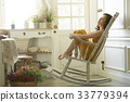 Relaxed girl is sitting on modern chair in light cozy room at home 33779394