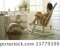 portrait of a girl sitting on the chair and looking outside 33779399