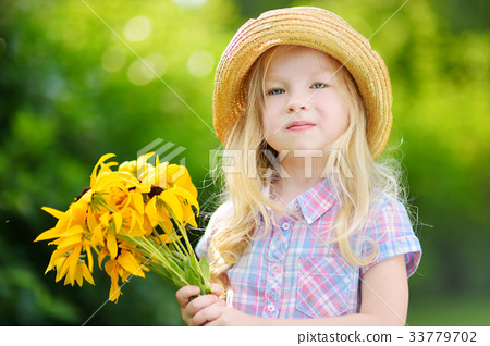Adorable little girl in straw hat holding beautiful yellow flowers 33779702