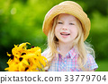 Adorable little girl in straw hat holding beautiful yellow flowers 33779704