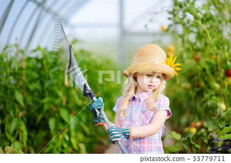 Adorable little girl wearing straw hat holding garden tools 33779711