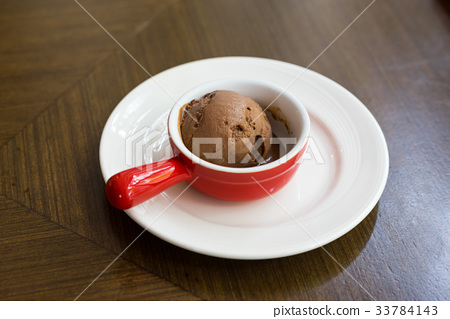 Chocolate ice cream in red cup. 33784143