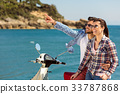 Couple sitting on motor scooter looking at each 33787868