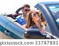 Couple with friends driving in the sunset 33787893