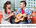 After moving together young man plays love song 33788944